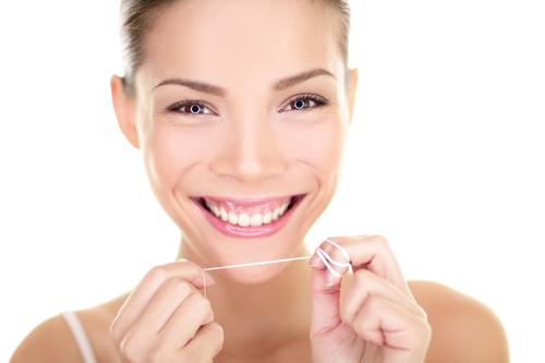 woman flossing dental crown